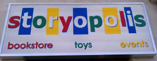 Storyopolis - Bright colors add playfulness and attention to the logo on a sign large enough to be seen by customers.